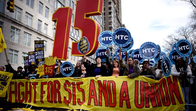 Workers hold signs as part of a day of rallies and protests by workers calling for fair labor practices and for the minimum wage to be raised to $15 per hour in New York, April 15, 2015.