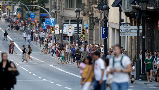 People walk down a main street in Barcelona, Spain, Thursday, Aug. 17, 2017.