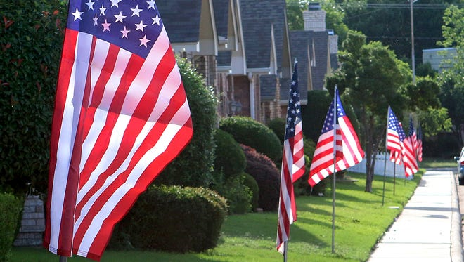 In this 2017 file photo, flags wave in the wind outside of homes along Kingsbury Drive for Memorial Day.