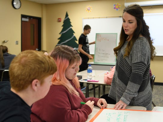 Math teacher Kendra Barrett answers a question as students work in groups to solve a geometry problem at Gibson Southern High School.