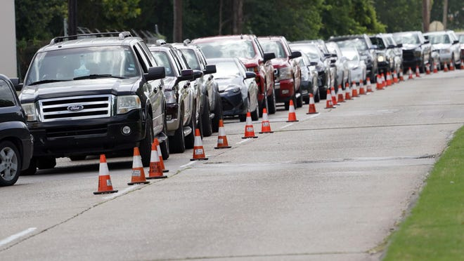 People wait inside their vehicles in line at a COVID-19 testing site Wednesday in Houston. The state  surpassed 10,000 new coronavirus cases in a single day Tuesday for the first time.