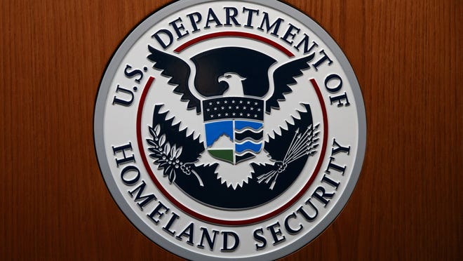 The Department of Homeland Security (DHS) seal is seen during a 2018 news conference in Washington. An official at the Department of Homeland Security says he was pressured by agency leaders to suppress details in his intelligence reports that President Donald Trump might find objectionable, including intelligence on Russian interference in the election and the threat posed by white supremacists.