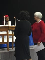 "Sister Sue Simmons, of Church of the Brethren, lights the second candle alongside Pastor Doris Woodson, of Friendship Church, ahead of the ""Prayer for Unity"" at the Staunton Branch NAACP's ""Unity Prayer Breakfast"" on Saturday, Feb. 4, 2017, at St. Paul's United Methodist Church in Staunton, Va."