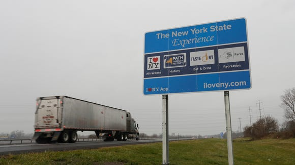 """A truck passes a sign for """"I Love New York"""" and other state attractions on the New York State Thruway, Tuesday, Nov. 29, 2016, in Utica, N.Y. Officials with the Federal Highway Administration and the New York Department of Transportation will meet in December to discuss the removal of more than 500 """"I Love NY"""" signs from the state's roadways. FHA officials say the signs don't conform to federal standards and pose a dangerous distraction for motorists. (AP Photo/Mike Groll)"""