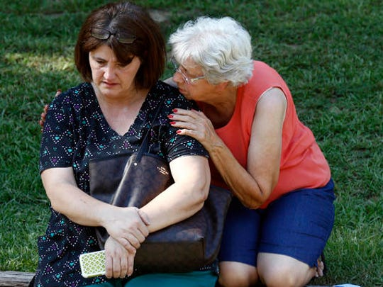 Jonell Payton, right, comforts Lisa Dew, outside the Durant, Miss., home of two slain Catholic nuns, Thursday, Aug. 25, 2016. The nuns worked as nurses at the Lexington Medical Clinic, where Dew was the office manager. Dew and a Durant police officer discovered their bodies inside the house after both nuns did not report for work. (AP Photo/Rogelio V. Solis)
