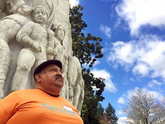 In this March 30, 2017, photo, Moses Maldonado poses for a photo in front of a statue depicting pioneers in front of the Oregon Capitol in Salem, Ore. Maldonado, who attended a rally honoring farmworker organizer Cesar Chavez at the Oregon statehouse, is a 50-year-old undocumented farmworker who says he is afraid he will be picked up by federal immigration authorities when he leaves his house to go to the fields.