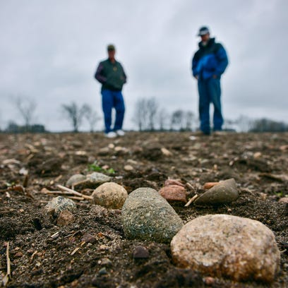 Butch Goldenstein examines a rock to determine if it's an agate April 19 in a field outside St. Stephen. Goldenstein started collecting Lake Superior agates as a child. He started cutting, polishing and making jewelry at age 10.