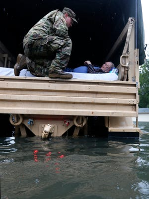 Members of the Louisiana Department of Wildlife and Fisheries, the Florida Fish and Wildlife Conservation Commission, and the Louisiana National Guard help rescue with elderly people from the Golden Years Assisted Living home, which was flooded from Tropical Storm Harvey in Orange, Texas, Wednesday, Aug. 30.