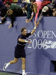 Todd Martin celebrates a five-set win over Carlos Moya in the fourth round of the 2000 US Open by running around the court and greeting fans.