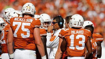 Texas Longhorns offensive coordinator Jay Norvell with the offense during a timeout against the Oklahoma Sooners during Red River rivalry at Cotton Bowl Stadium last season.