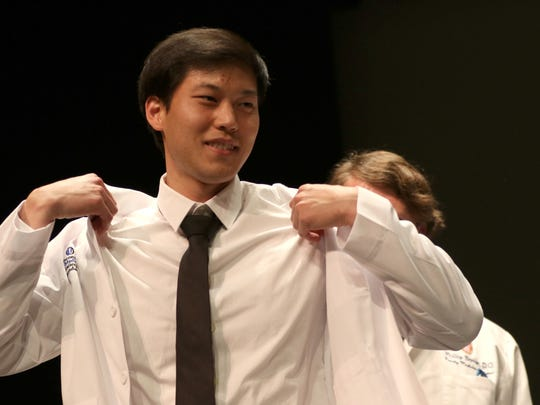 Andrew Guo is coated during the Medical College of Wisconsin Central Wisconsin White Coat Ceremony at UW Marathon County, in Wausau, Wisconsin, July 7, 2016.