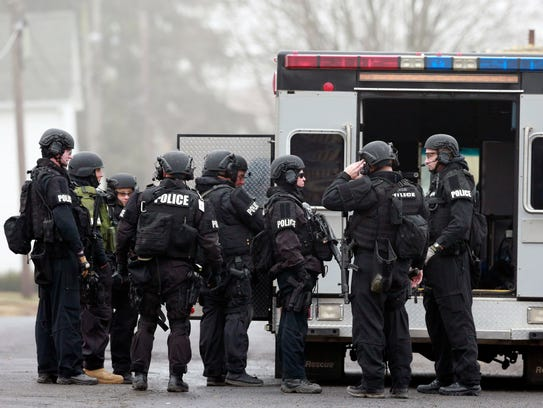 Police gather at a staging area as they search for
