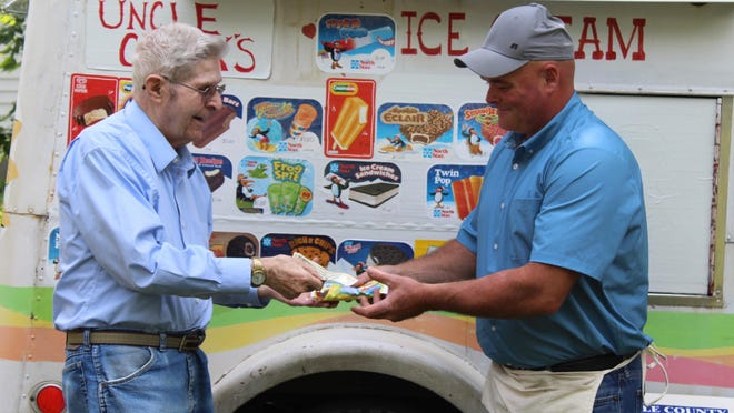 Gary Scoville passes on the ice cream tradition to Chuck Howe, who is continuing to sell ice cream treats four days a week in and around Hillsdale.