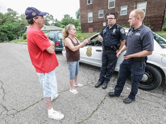IMPD patrolman Adam Perkins, center, and CORE paramedic Shane Hardwick, right, are flagged down by Beverly McCray and her partner, Frank Richard, looking for McCray's daughter who is battling drug addiction and wanted on warrants, Wednesday, June 15, 2016.