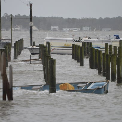 A wave-swamped boat bobs in Indian River Bay east of