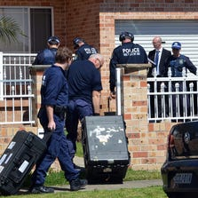 Forensic experts collect evidence from a house in the Guildford area of Sydney on September 18, 2014.
