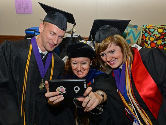 Joshua Steinke of Many, left, and Courtney Coriell of Leesville, right, take a photo with Northwestern State Associate Professor of Marketing Begona Perez-Mira prior to afternoon spring commencement exercises at Northwestern State University on Friday. Steinke and Coriell graduated summa cum laude with grade point averages of 3.9 or better.