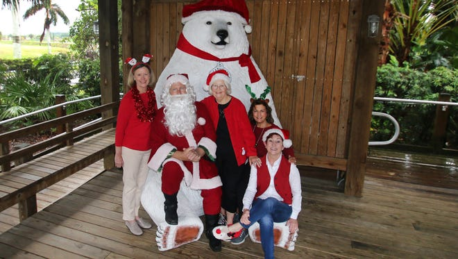Organizing members of Impact 100 St. Lucie sitting with Santa Claus are Linda Chastain, left, Cris Adams, Lisa Floyd, and Debbie Butler. The picture was taken at Heathcote Botanical Gardens.