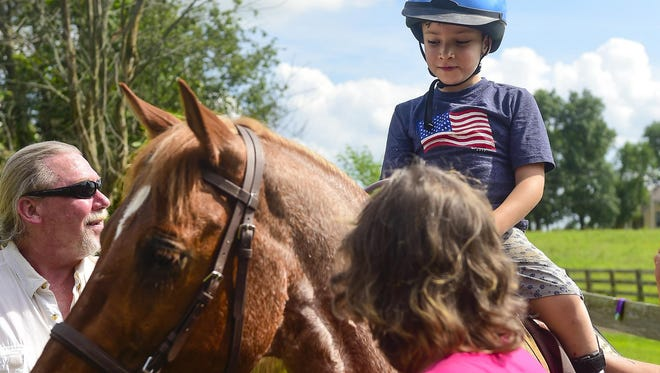 Seven-year-old Dominic Amesquita sits atop Will during a session at the Providence Therapeutic Equestrian Center.