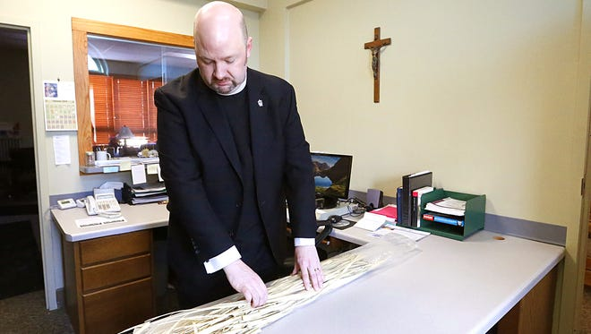 """St. Paul's Cathedral's Rev. C. Patrick Perkins readies old palm leaves Saturday to be turned into ashes for Ash Wednesday. The Fond du Lac church will offer """"Ashes To Go"""" for people unable to attend the full Mass on Wednesday. They will be able to drive by the Division Street church and get their ashes while remaining in their vehicle."""