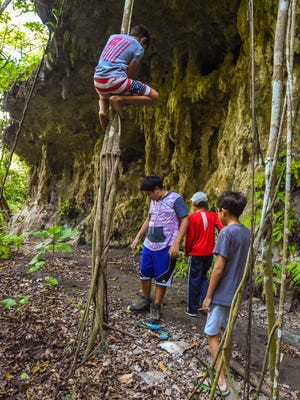 Keanu Anderson, 11, tries his hand, and feet, at climbing intertwined viines hanging from the cliffline of Guam National Wildlife Refuge, Puntan Litekyan (Ritidian Point Unit), during a group tour in the area on Saturday, Feb. 17, 2018.