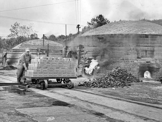 """Clarence Watts pushes a load of dried bricks past of one of the kilns at the Medora Brick Co. in 1954. The """"green"""" bricks will be put into a kiln and burned for five days to give them the red look."""