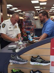 In support of a previous Mend Mansfield Coalition's shoe drive, Mansfield Police Capt. Bret Snavely purchased 87 pairs of kids shoes at the Shoe Department in the Richland Mall.
