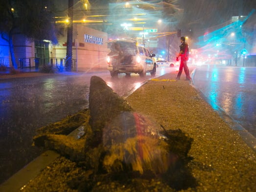 Phoenix Police pull a downed palm tree out of Van Buren Street after Thursdays storm came through Phoenix. Dave Seibert/The Republic