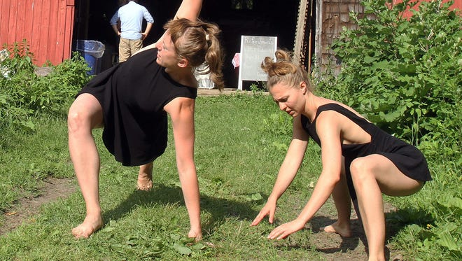 From left, Dancers Jessica Parks and Cat Murcek stretch outside an old barn at Ryder Farm in Brewster as they wait their turn to take the stage in the barn on June 25.