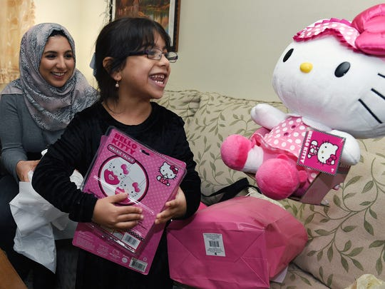 Syrian refugee Ghadeer Nakshou, 5, smiles after receiving Christmas presents as a family friend, Dima Sbenaty, left, helps opens her gifts given by United Methodist Communications staff on Thursday, Dec. 17, 2015.