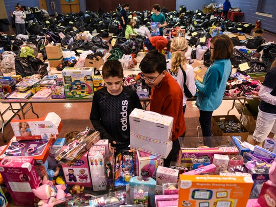 New Covenant Christian School students Trenton Vanderploog, 13, left, and Patrick McLaughlin, 13, right, pick out toys for distribution in the Lebanon Salvation Army's Angel Tree program Thursday, Dec. 17, 2015. The program will help 270 needy families, but Capt. Ernesto Portillo and his wife Capt. Amy Portillo. However, expect that number could rise to 300 families, which will include between 800 and 1,000 children.