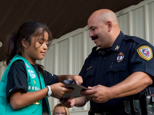 Zoe Dereef receives a plaque from Chambersburg Police Chief, Ron Camacho, during a ceremony honoring Troop 80067 on Thursday, Sept. 15, 2016 in Chambersburg, Pa. The troop sold 8200 boxes of cookies.
