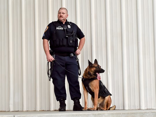 Corporal Michael Taylor of Chambersburg Police Department stands next to K9 Rownan, a Belgian Malinois, stand on stage during a ceremony honoring Chambersburg Girls Scout Troop 80067 on Thursday, Sept. 15, 2016 in Chambersburg, Pa. K9 Rownan is wearing the bullet proof vest that the girls fundraised for.
