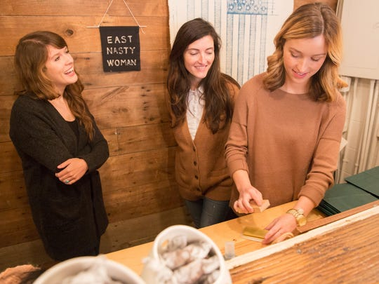 From left, Hey Rooster General Store employee Meredith Kane talks with owner Courtney Webb as employee McKenzie Teasley stamps store bags inside Hey Rooster General Store during the Gallatin Galavant on Small Business Saturday.