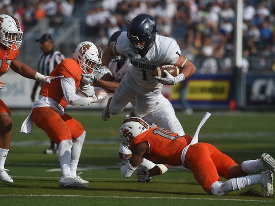 Nevada receiver McLane Mannix tries to doge the Idaho State defense during last season's game in Reno.