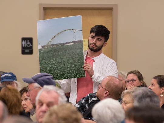 A photo showing solid waste being sprayed on to a field is held up for all to see during a meeting with Mountaire Farms officials to discuss high levels of nitrates in the ground water.