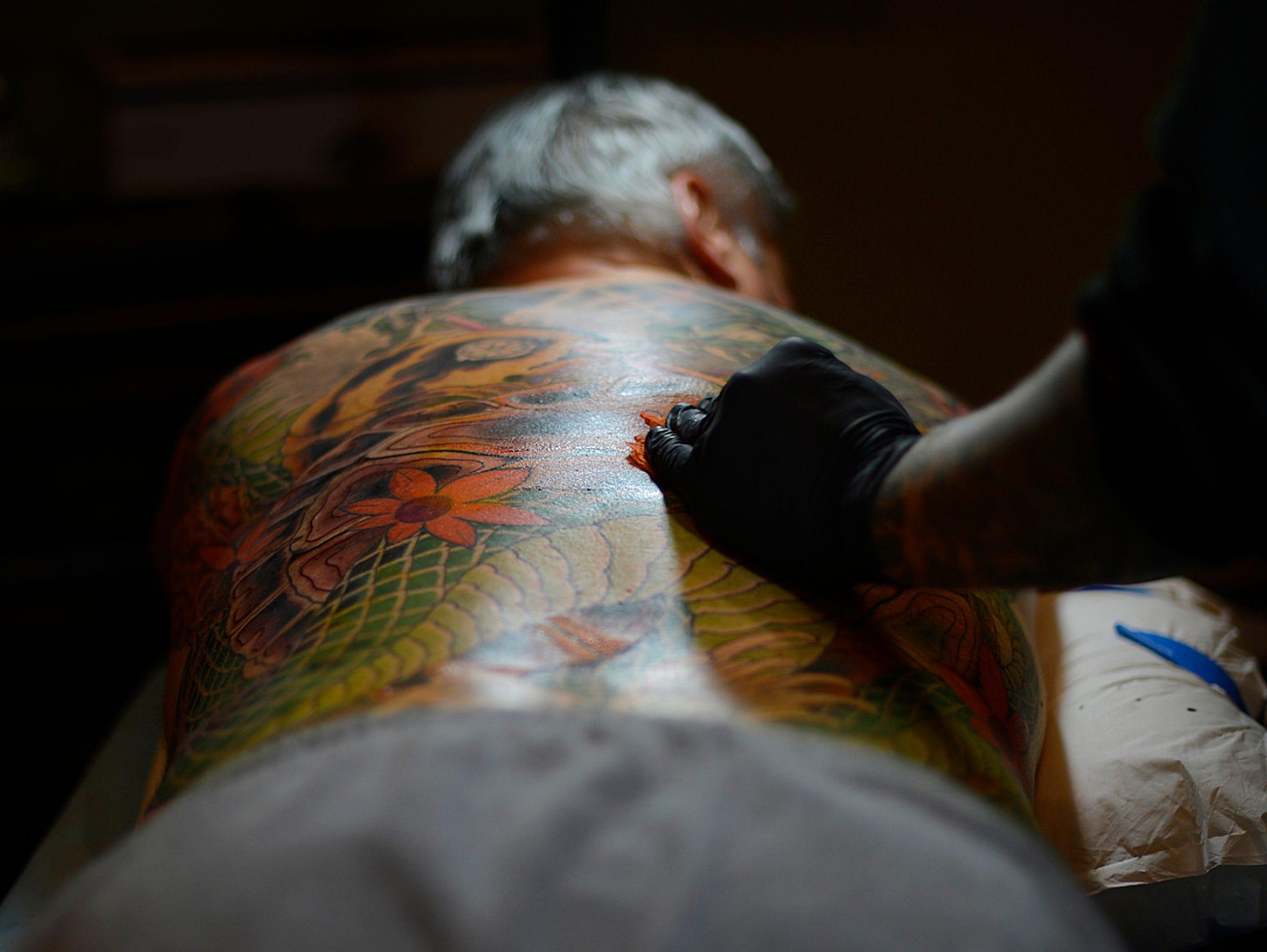 Tattoo artist Paul Dhuey works on John Utrie's back