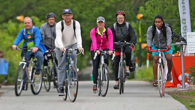 Co-workers with NextGear Capital, Bob Plank, from left, Dan, Gillison, Lucas Hancock, Stacey DeClue , Patty Turner, and Qaniah Douglas,  continue to work after stopping at the Monon Community Center, as they bike along the Monon for National Bike to Work Day, Friday, May 20, 2016.