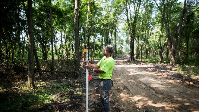 Allen Byler measures a prospective trailway at the Red-tail Conservancy's Dutro-Ernst Woods on Kilgore Avenue near the old Borg Warner plant Tuesday morning.