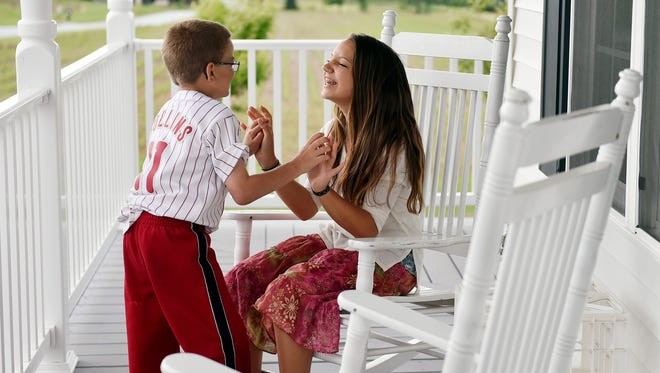 Sean Kisielnicki, 7, and sister Emma, 13, tease each other on their grandmother's Hopewell Township porch Wednesday, June 7, 2017. Emma, who is the second-oldest of six children, acts as Sean's second mother. Sean Kisielnicki, 7, is the second-youngest of six children in his tight-knit family, who live on eight acres in Hopewell Township with a large garden and a menagerie of animals. Sean is diagnosed with Hunter syndrome — a terminal genetic enzyme deficiency that affects 400-500 people in the U.S. and that, for Sean, brings an array of accompanying conditions such as autism, attention deficit hyperactivity disorder and sensory processing disorder. The Kisielnicki family, whose children range in age from 5 to 15, have structured their lives around caring for Sean, whose high-energy presence requires constant supervision and who receives weekly in-home enzyme replacement therapies.