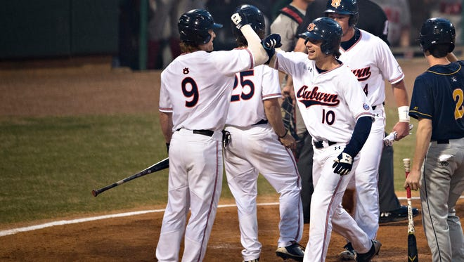 Auburn player Edouard Julien (10) celebrates with Alabama infielder Cody Henry (9) after hitting a home run during the Capitol City Classic between Alabama and Auburn on Tuesday, March 27, 2018, in Montgomery, Ala.