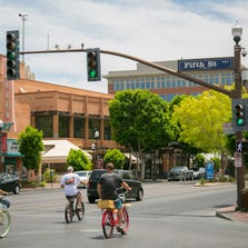 Bikes ride next to cars down the streets on Mill Avenue in Tempe in June 2014.