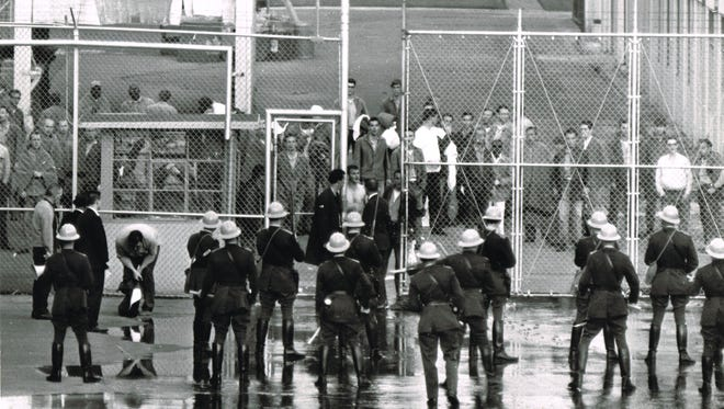 Correctional Officer Francis Petrie (left) bends to remove the convict clothing he wore as a disguise to get out of the yard on March 9, 1968, where he had been held hostage by rioting inmates at the Oregon State Penitentiary. Correctional Administrator George Randall talks to convicts through wire fence as armed police stand guard at an open gate as inmates gathered at inner fence. The photo was taken by Oregon Statesman photographer John Ericksen and was on the front page of the March 10 newspaper.