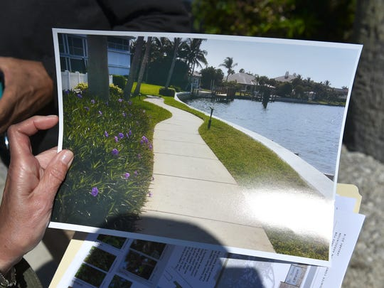 """Judi Honiss, landscape chairman for The Pointes in The Moorings, holds a """"before"""" photo of landscaping of tropical plants along the riverfront, that have since been replaced with lagoon-friendly Florida native plants."""