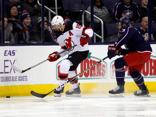 New Jersey Devils forward Travis Zajac, left, chases the puck against the Columbus Blue Jackets defenseman Seth Jones during an NHL hockey game in Columbus, Ohio, Tuesday, Dec. 5, 2017. The Devils won 4-1. (AP Photo/Paul Vernon)