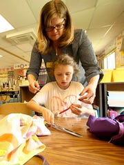 Meloni Courtway helps Tori Youle, 9, cut a ribbon to make a ties of one of the pillowcase dresses.