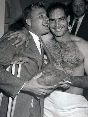 Lions quarterback Bobby Layne, left, who broke his ankle prior to the game, hugs quarterback Tobin Rote after the Lions beat the 49ers, 31-27, in the Western Conference championship in this Dec. 22, 1957 file photo in San Francisco.