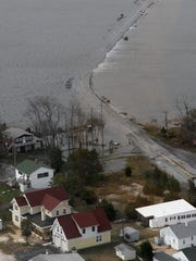 Prime Hook Road, stretching through the marsh to Primehook Beach, is under water the day after Sandy made landfall.