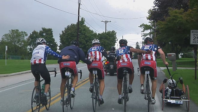 """Cyclists from Ride 2 Recovery push one another up a hill during a commemorative 9/11 ride from the documentary """"Recovering."""""""