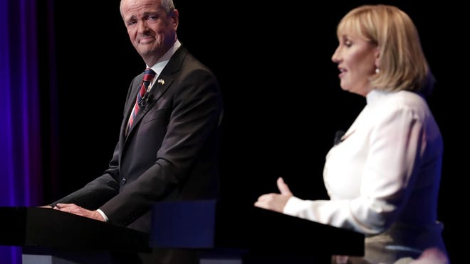 Democratic gubernatorial nominee Phil Murphy, left, listens as Republican nominee Lt. Gov. Kim Guadagno answers a question during a gubernatorial debate at the New Jersey Performing Arts Center in Newark on Tuesday